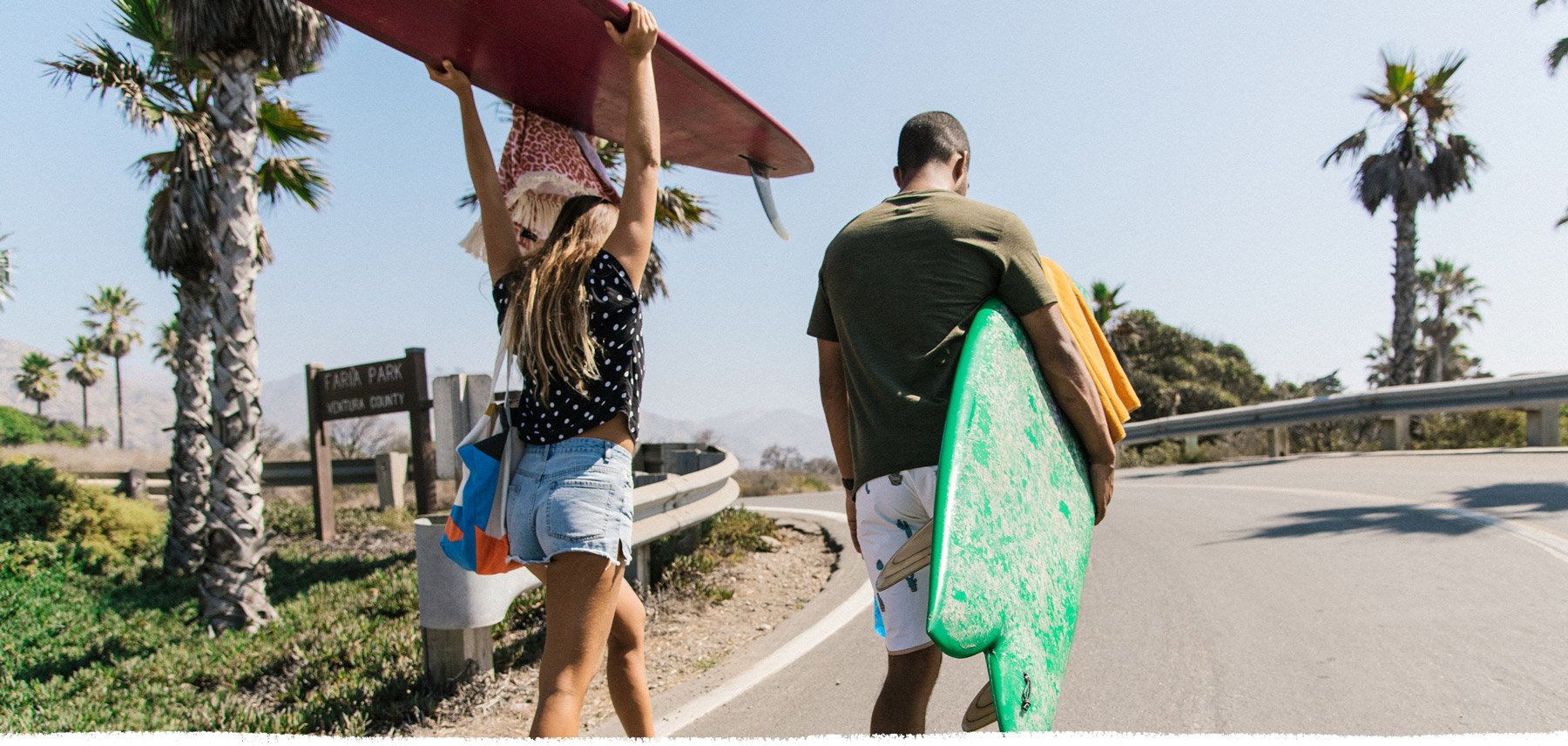 Man and woman carrying surfboards.