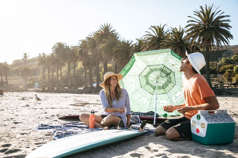 Two people sitting on a beach with a Sanuk Beach Umbrella.