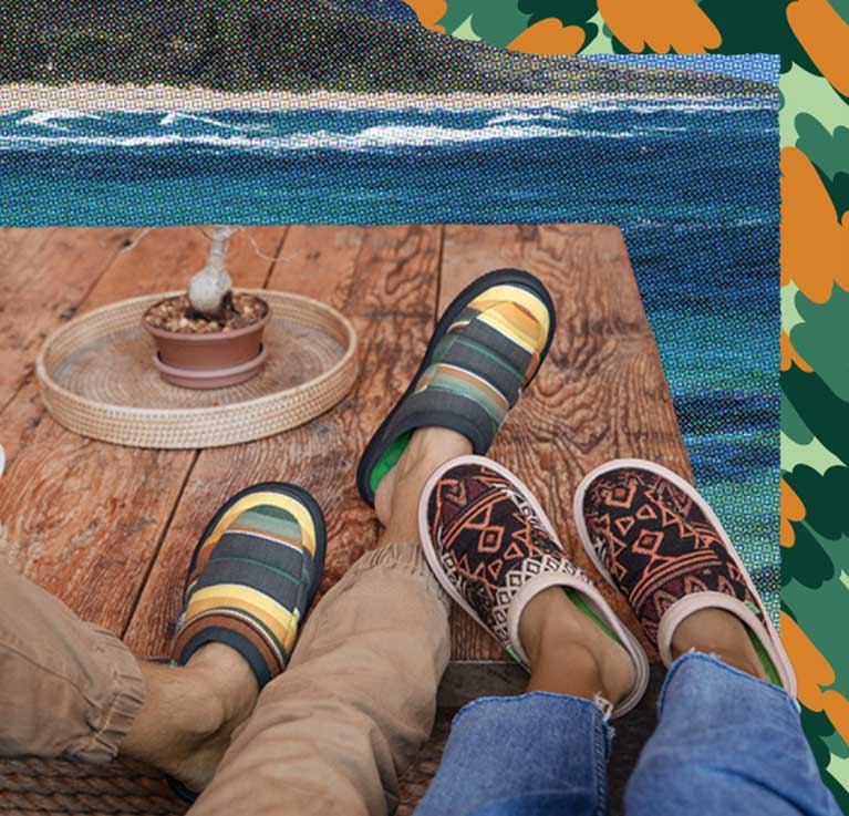 Couple wearing Sanuk shoes near a fire.