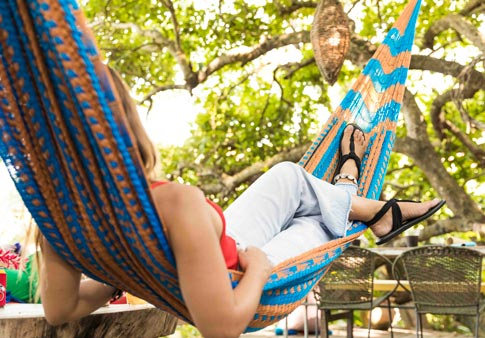 ddb85e3bd61b15 Woman wearing Yoga Sling Ella while lounging in a hammock.