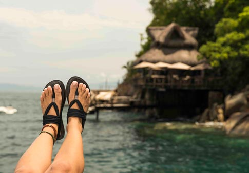 ca8f581273c0 Woman wearing Yoga Sling sandal kicks her feet up in front of a hut on the