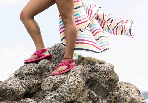 dfe69e35df8404 Woman wearing Yoga Sling 2 Spectrum while standing on top of a rock at the  beach