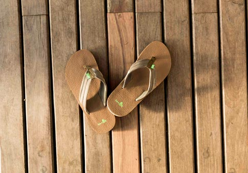 5aaa41e5c1c Men s Land Shark sandals propped on a wood deck.