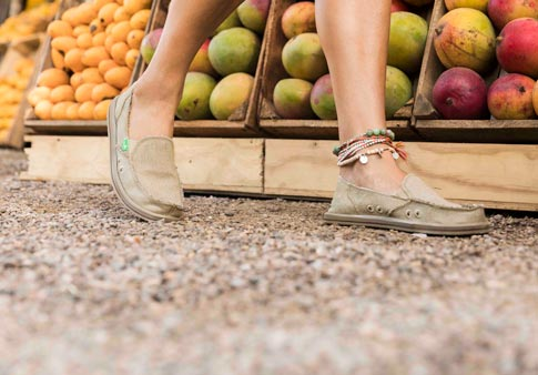 40e44c778ce Woman wearing Donna Hemp shoe while standing in front of a fruit stand.