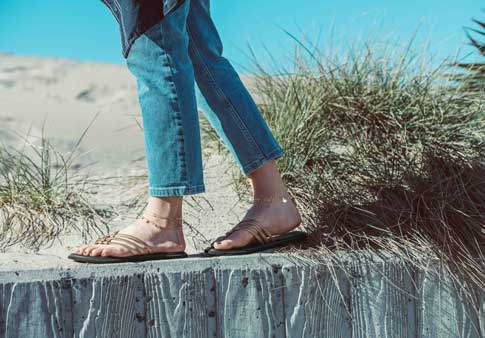 2d39cfb2366d33 Woman wearing Yoga Salty Metallic sandal while walking on a wall at the  beach.