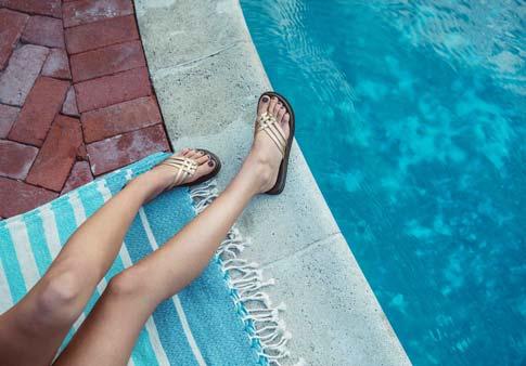 66ea4171a3adad Woman wearing Yoga Salty Metallic sandal while lounging on a blanket near  the pool.
