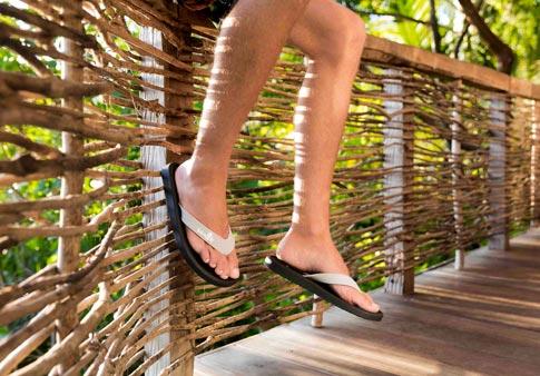 b157e93bc1c Man wearing Sidewalker sandal while sitting on a balcony.