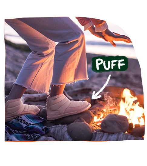 A woman stepping toward a campfire in the Sanuk Puff n Chill