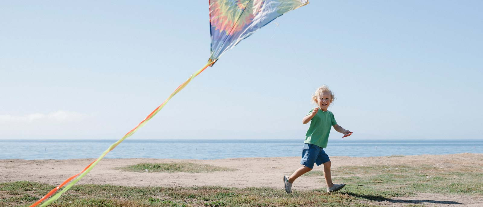 Kid flying a kite on the beach, wearing Sanuks.