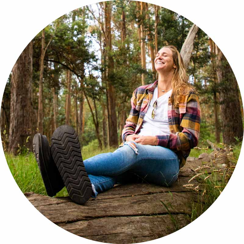 Woman sitting on a log in the forest in the Chiba Journey LX.