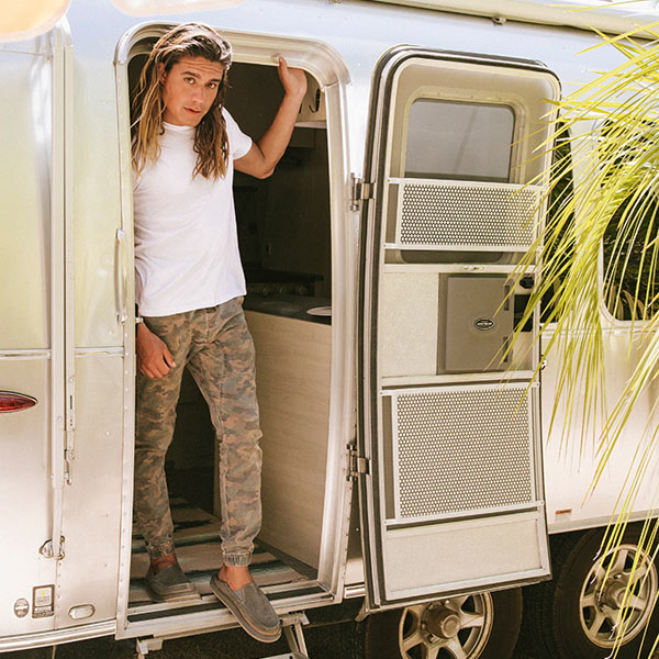 A person, wearing Sanuk Sandals, standing in a doorway of an Airstream.