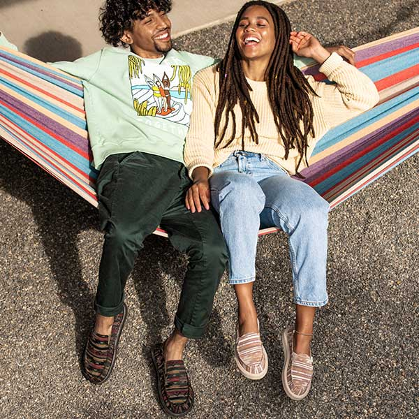 Man and woman lounging in a hammock, wearing Sanuk Soft Top Sandals.