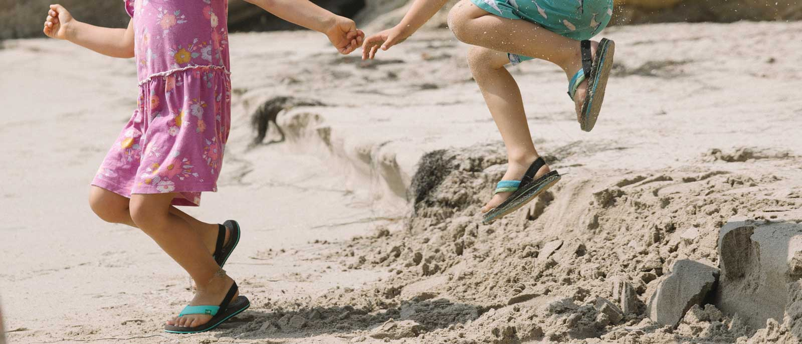 Little boy and girl playing on the beach, wearing Sanuk sandals.
