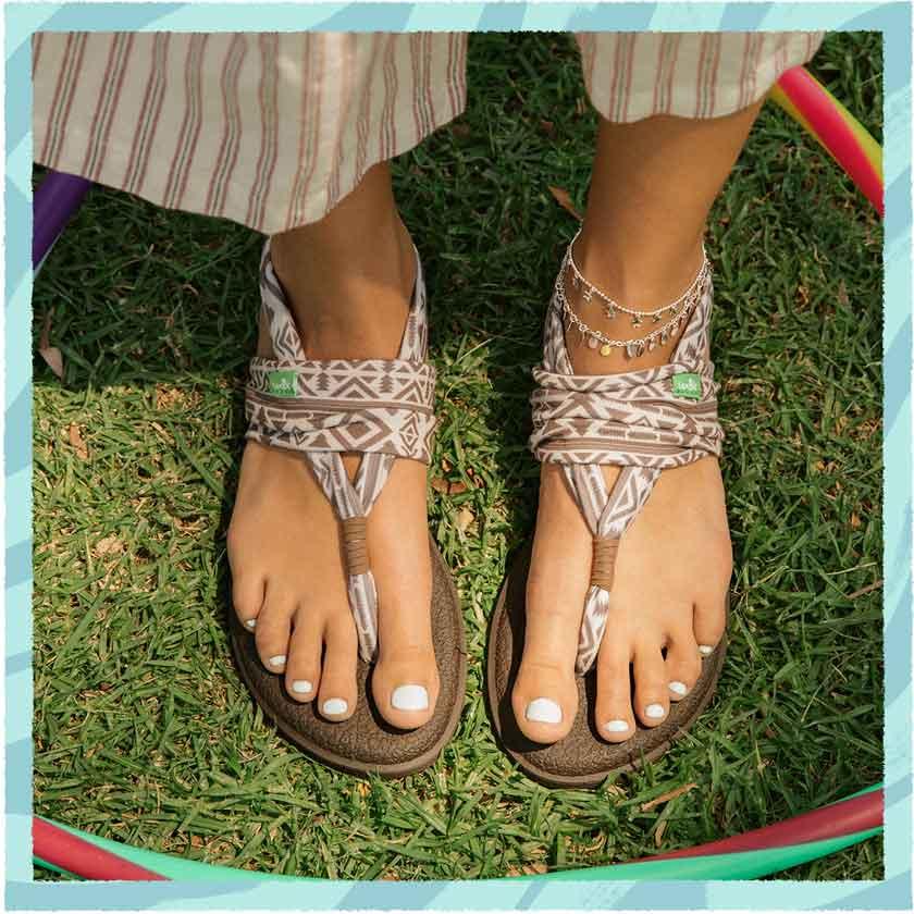 Feet standing in a hoolahoop wearing Sanuk Print Sandals