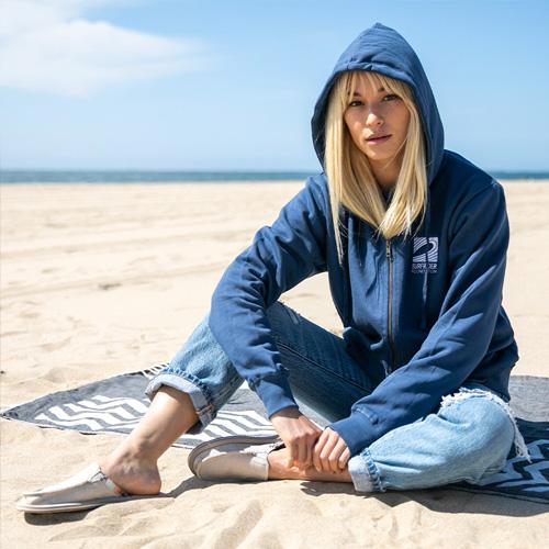 A woman, sitting on a beach, wearing Sanuk Sandals.