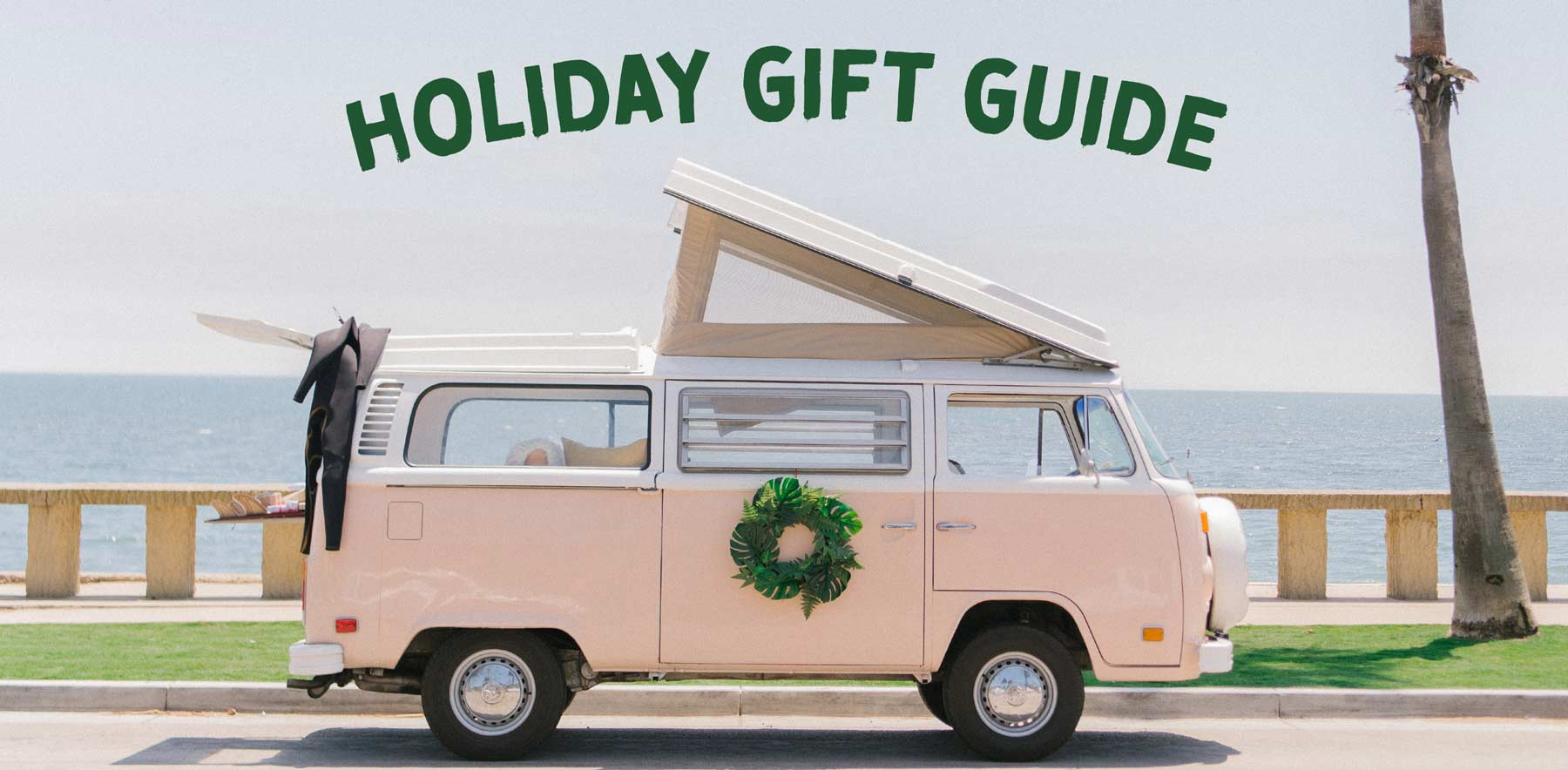 Pink van parked near the beach beside text of Holiday Gift Guide.