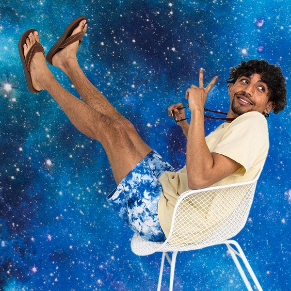 A person, wearing Sanuk Yoga Comfort Sandals, sitting in a chair with a space-themed background.