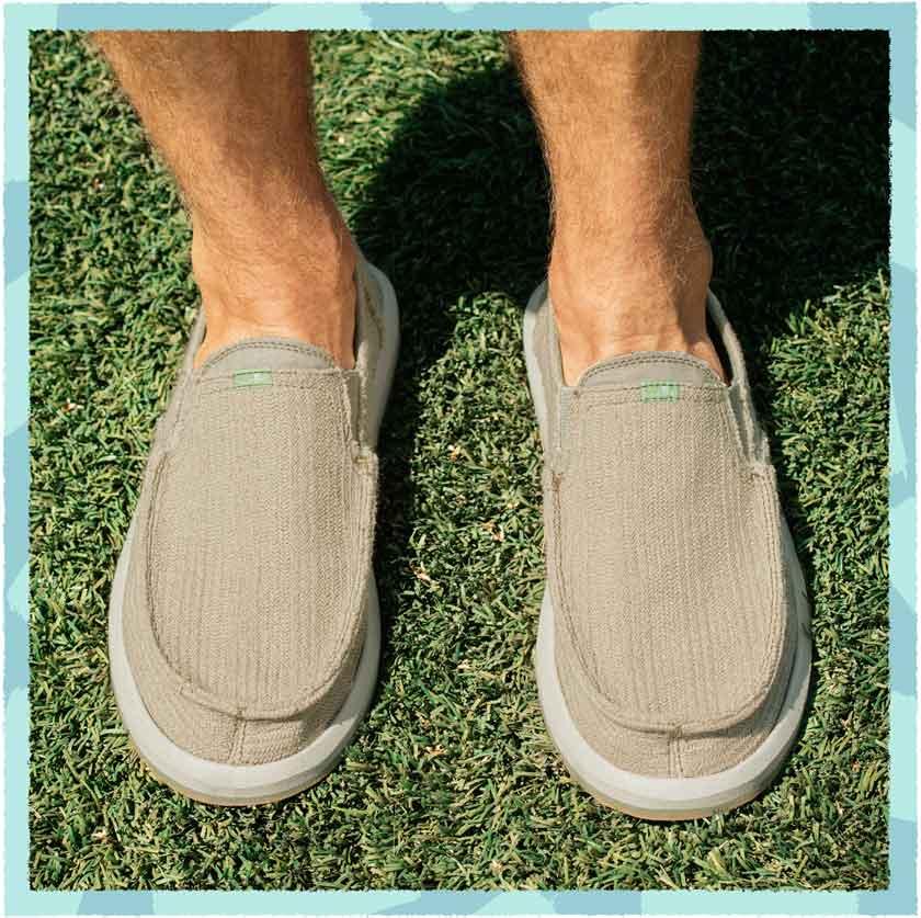 Feet standing on grass wearing Sanuk Vegan Sandals
