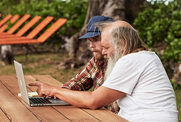 Rick Rubin looking at a laptop with a Sanuk designer.
