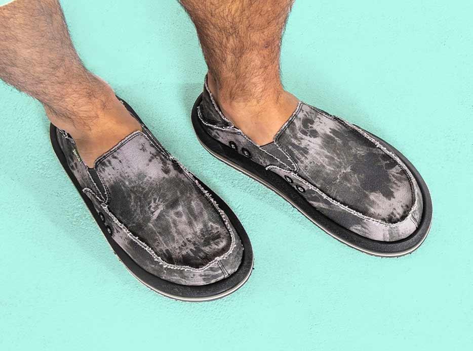 A close up of a man wearing Sanuk Vagabond ST Tie Dye shoes.