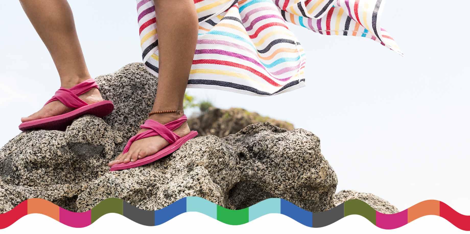 Woman standing on rock in flip flops