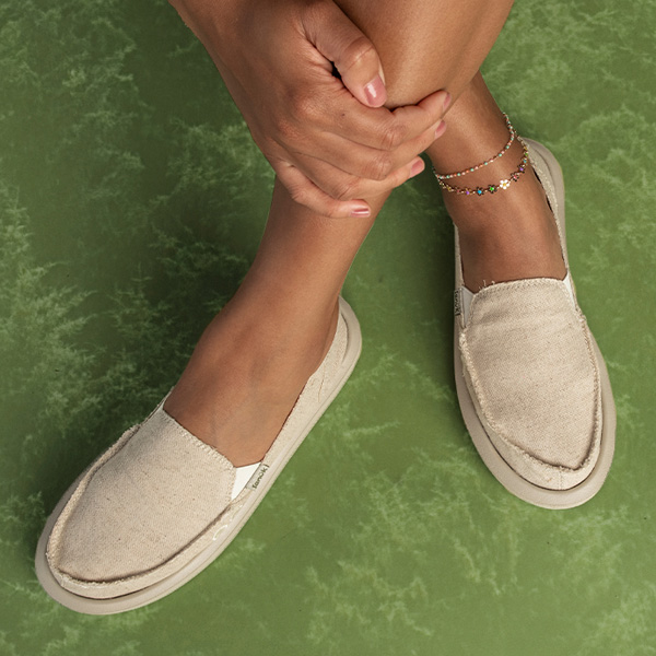 Close up of someone's feet wearing Sanuk shoes.