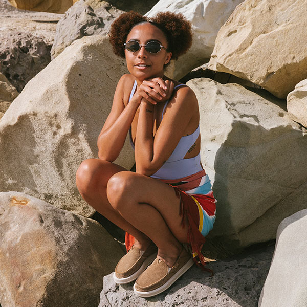 A person, wearing Sanuk Sandals, crouching on a rock on a beach.