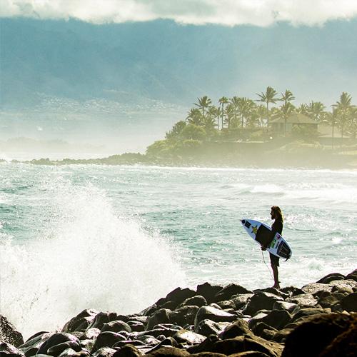 A man, holding a surfboard, standing on a rocky beach.