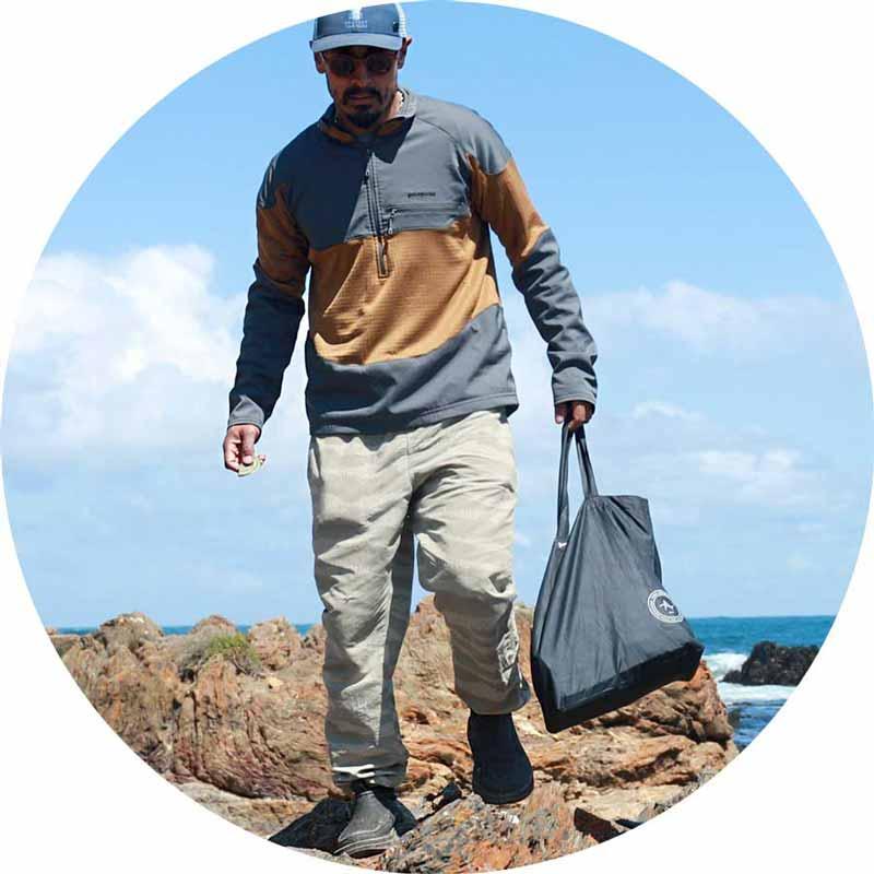 Man walking across a rock near the ocean in the Chiba Journey LX.