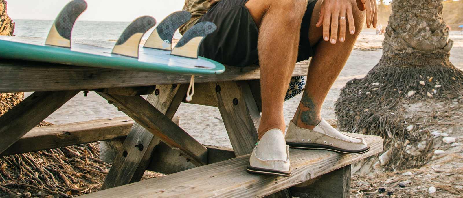 Man sitting on park bench next to his surfboard, wearing Sanuks