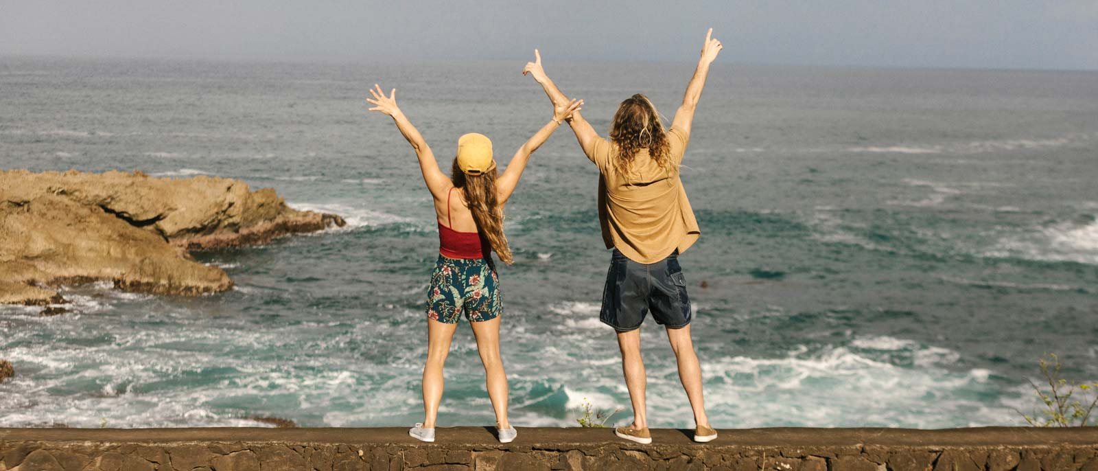 Man and woman standing on wall by ocean, wearing Sanuks.