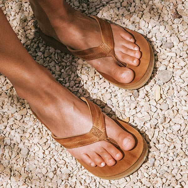 Close up of someone's feet wearing Sanuk Sandals.