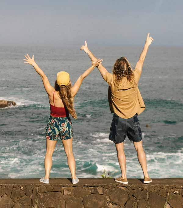 Man and woman at the ocean with arms raised and backs facing the camera.