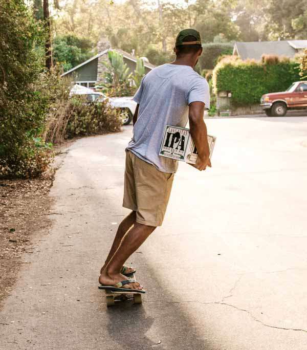 Man wearing Sanuk sandals riding a skateboard.