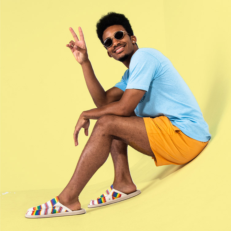 Somone sitting, wearing Sanuk sandals, giving the peace sign.