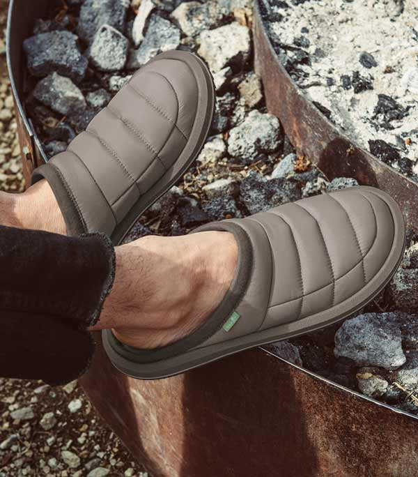 Man wearing Sanuks with his feet up on the burntout Coals of an outdoor Firepit.