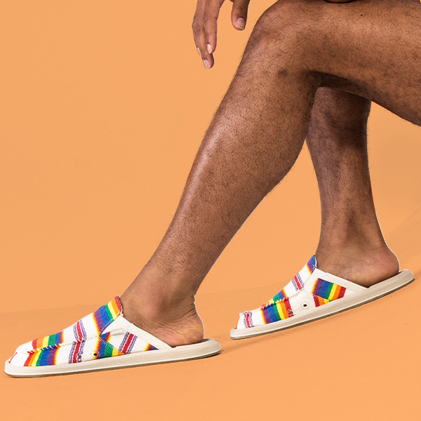 Close up of someone's legs wearing Sanuk sandals.