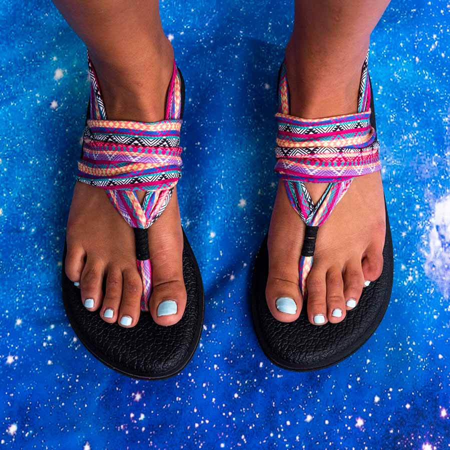 Close up of a woman's feet, wearing Sanuk Flip Flops.