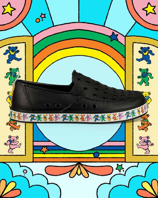 Black Sanuk and Grateful Dead slip-ons over a bright blue, sky-like pattern.