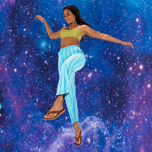 A person standing in front of a space themed background, wearing Sanuk Yoga Comfort Sandals.