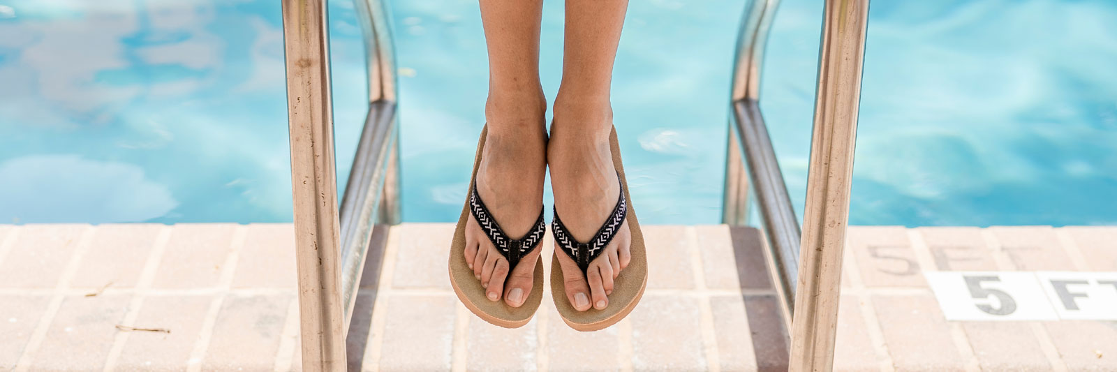 Close up of a woman's feet wearing Sanuk Sandals with a pool in the background.