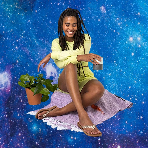 A person, wearing Sanuk Yoga Comfort Sandals, sitting on a blanket with a space-themed background.