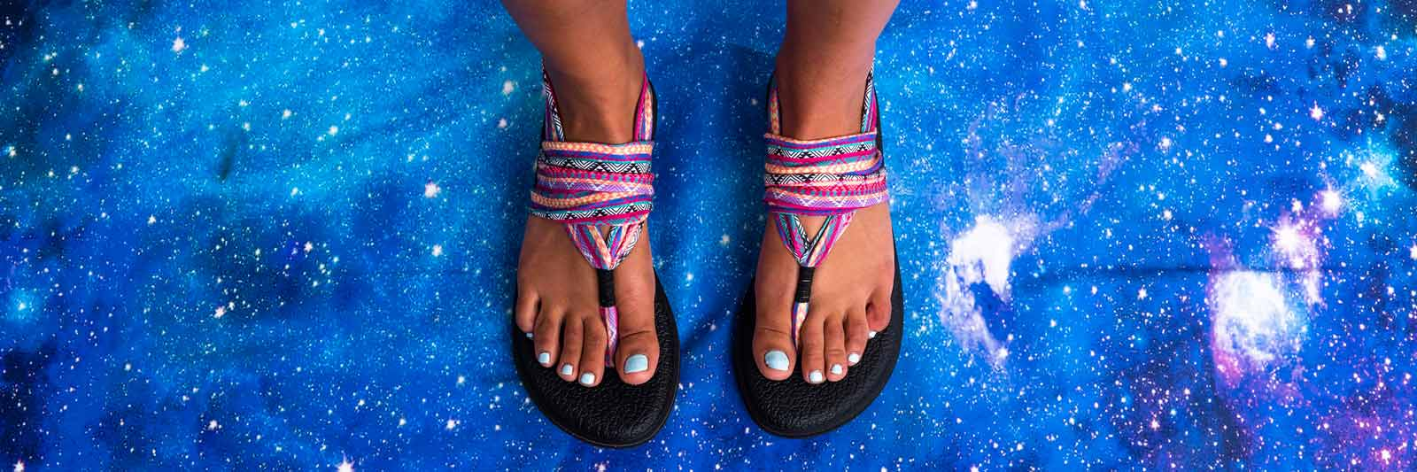 Close up of a woman's feet wearing Sanuk Flip Flops.
