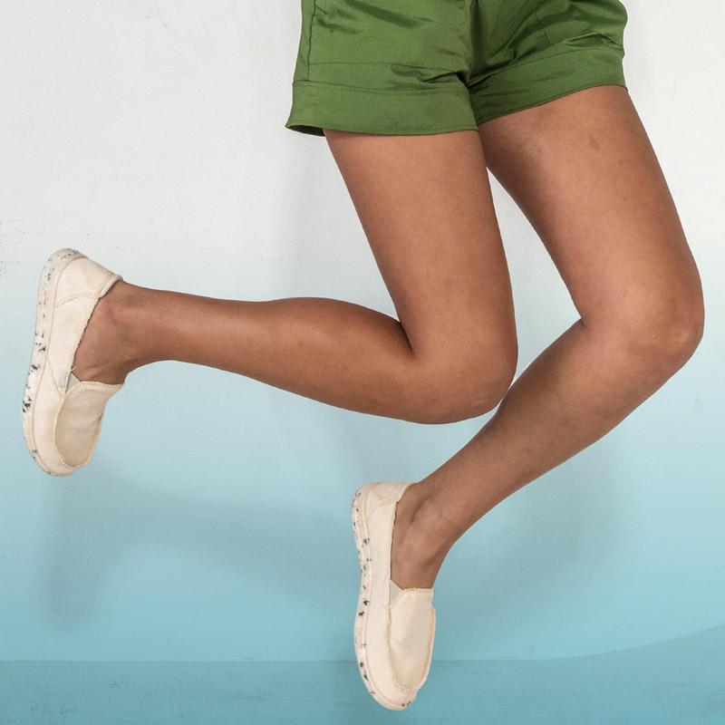 Women jumping wearing Sanuk recycled materials shoes.
