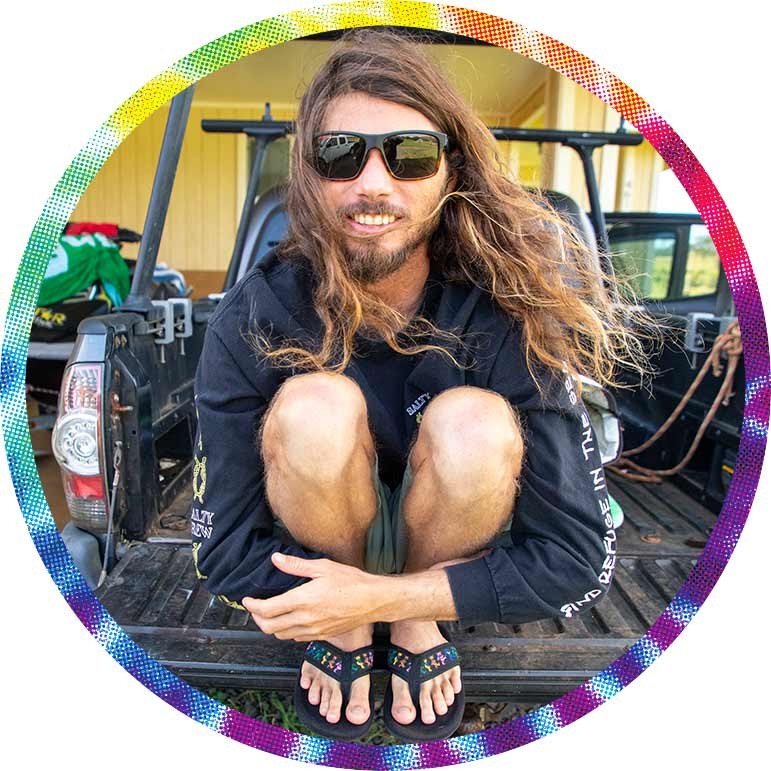 Long-haired man squatting in Grateful Dead flip-flops.
