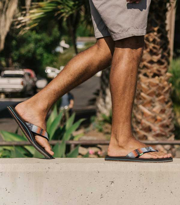 Man walking in his Sanuk Flip Flops, palm tree in background
