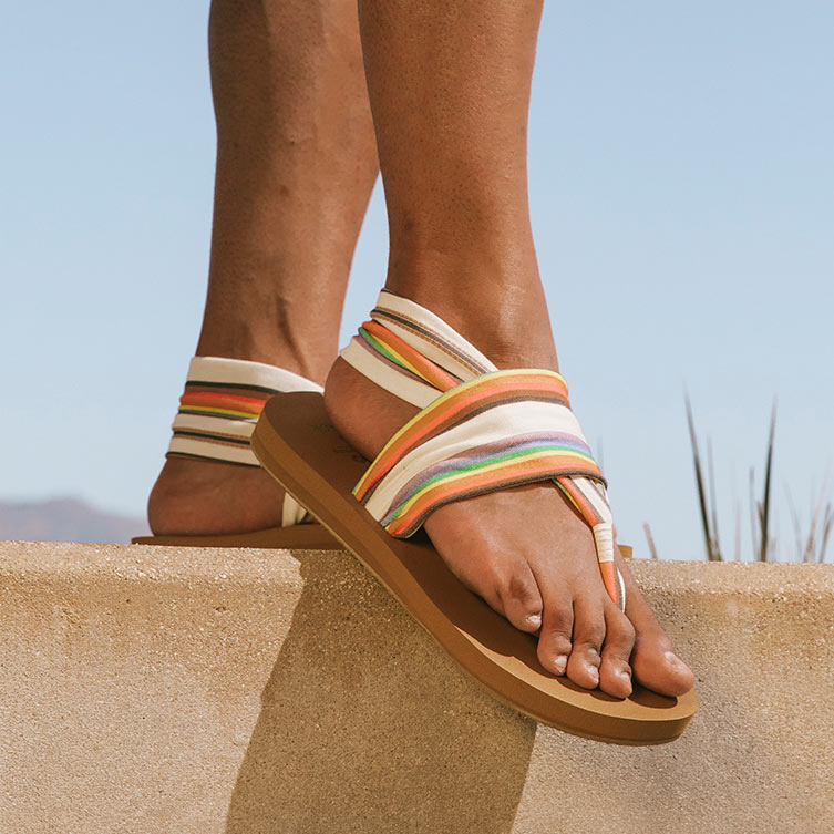 Close up of someone's feet, standing on a ledge, wearing Sanuk sandals.