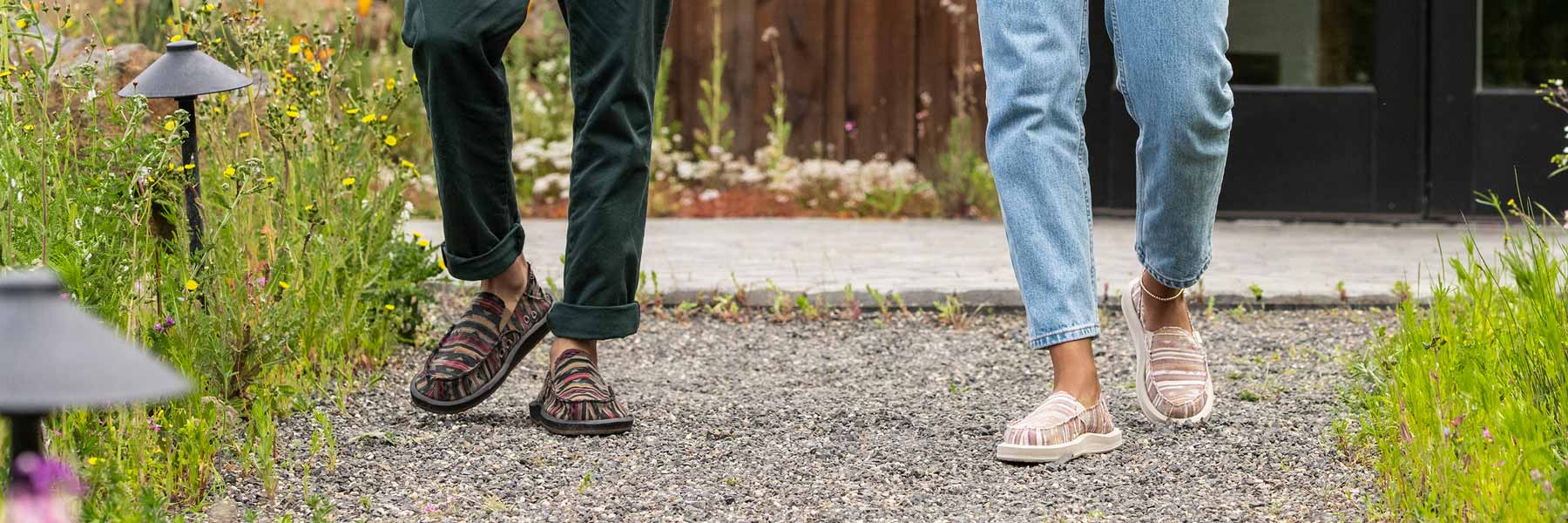 Close up of two people's legs, wearing Sanuk Shoes, walking down a path.