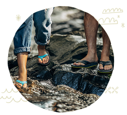 Man and woman walking on trail wearing Sanuk flip flops