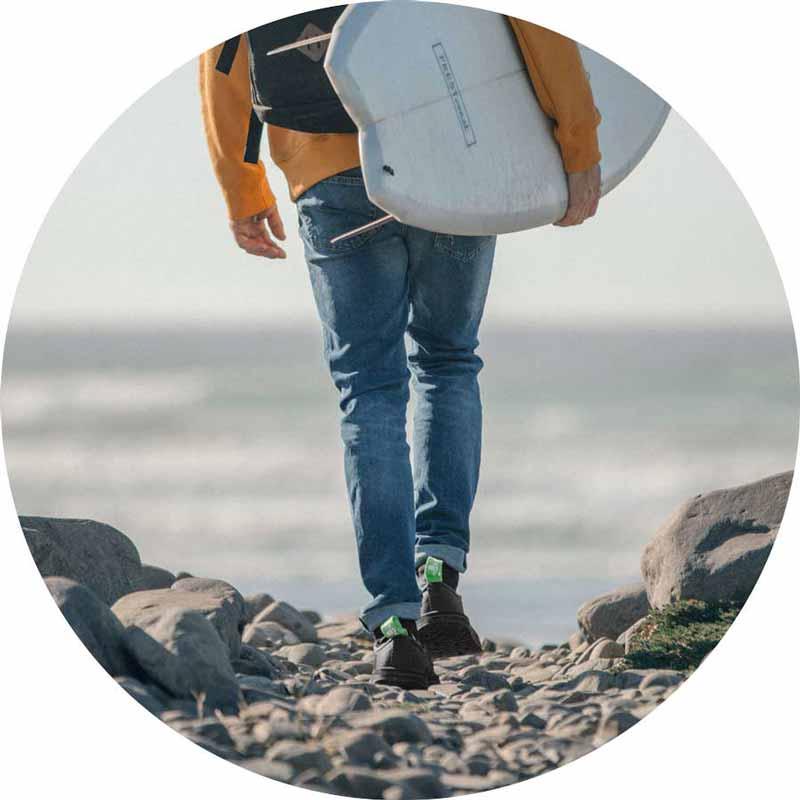 Man walking toward the beach across the rocks in the Chiba Journey LX.